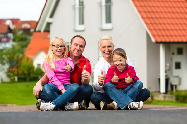 Stock photo: Family sitting in front of home