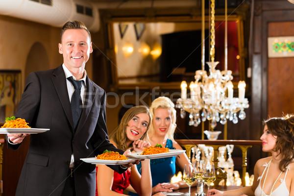 Amici ristorante cameriere servito cena bene Foto d'archivio © Kzenon