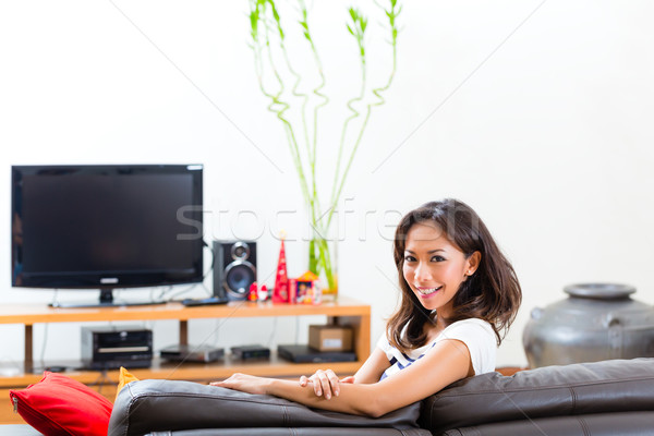 Young asian woman at home on the sofa Stock photo © Kzenon