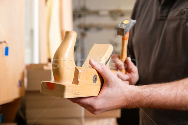 Carpenter with wood planer and hammer Stock photo © Kzenon