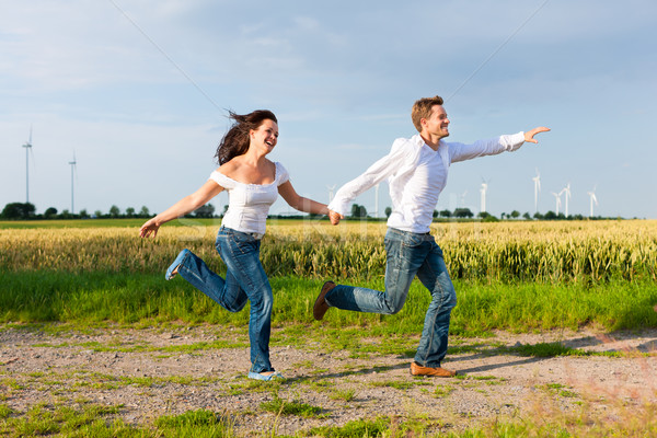 Happy couple running on a dirt road Stock photo © Kzenon