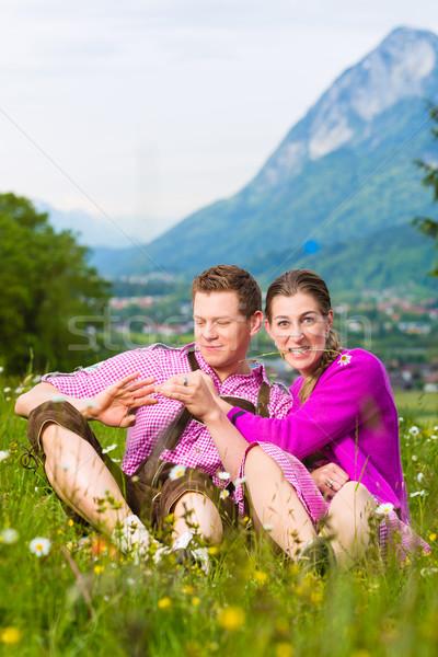 Para alpejski łące tradycyjny sukienka posiedzenia Zdjęcia stock © Kzenon