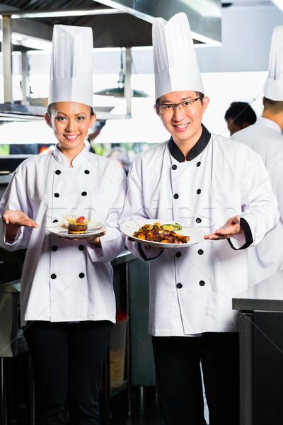 Asian Chef in restaurant kitchen cooking Stock photo © Kzenon