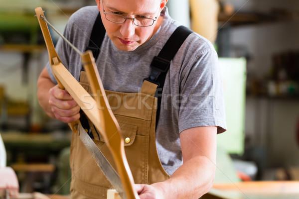 Carpenter using hand saw Stock photo © Kzenon