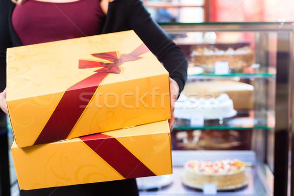 Woman presenting takeaway boxes of confectionery Stock photo © Kzenon
