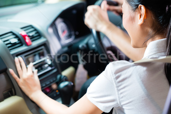Asian couple driving new car, she is turning on the radio Stock photo © Kzenon