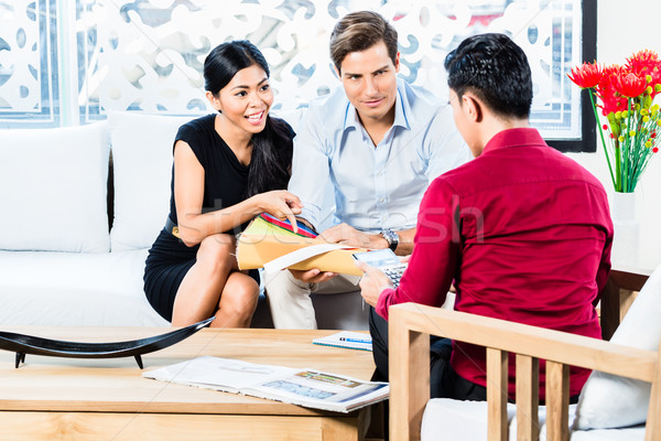 Couple in furniture store with shop assistant Stock photo © Kzenon