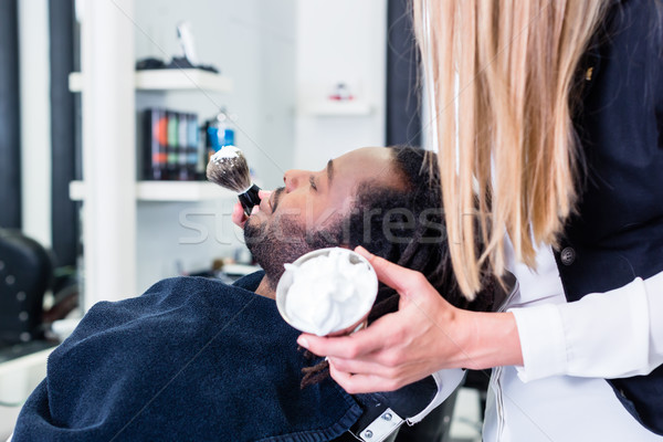 Barber soaping customer getting ready to shave him Stock photo © Kzenon