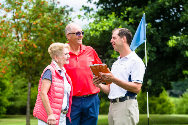 Golf pro with senior woman and man analyzing results Stock photo © Kzenon