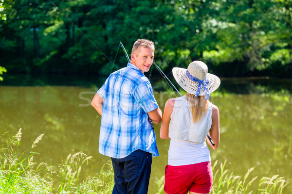 Young couple fishing or angling standing on river shore  Stock photo © Kzenon