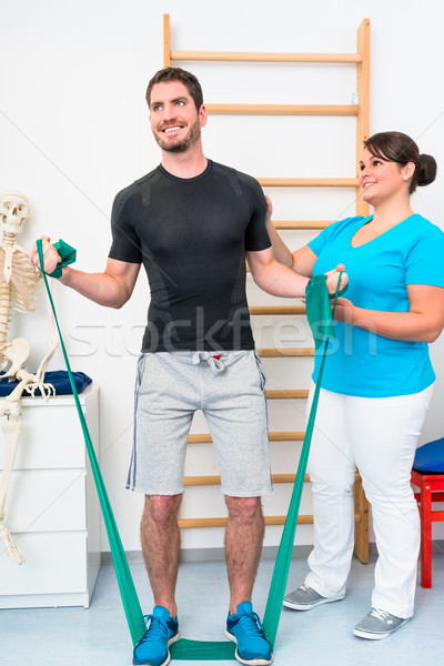 Young man exercising with resistance band in physical therapy Stock photo © Kzenon