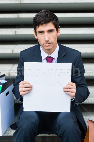 Young unemployed man showing blank white cardboard outdoors Stock photo © Kzenon