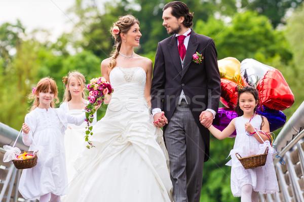 Wedding couple with flower children on bridge Stock photo © Kzenon