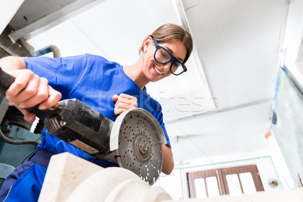 Female sculptor cutting stone with angle grinder Stock photo © Kzenon