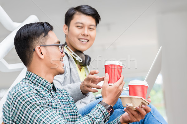 Two young Asian men using a laptop while relaxing during break Stock photo © Kzenon