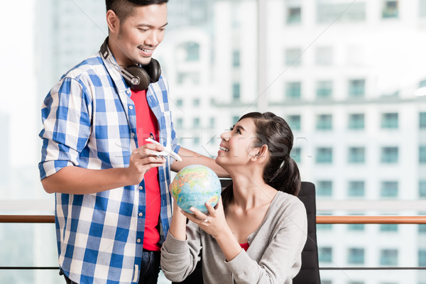 Asian couple with globe and model airplane in urban apartment Stock photo © Kzenon