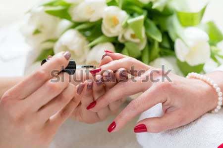 Close-up of the hands of a young woman with red polished nails i Stock photo © Kzenon