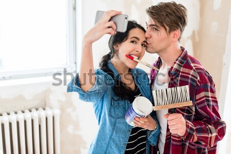 Young couple making a selfie while working to the renovation of their home Stock photo © Kzenon