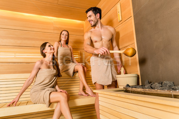 Young and beautiful people smiling while socializing in a wooden sauna Stock photo © Kzenon