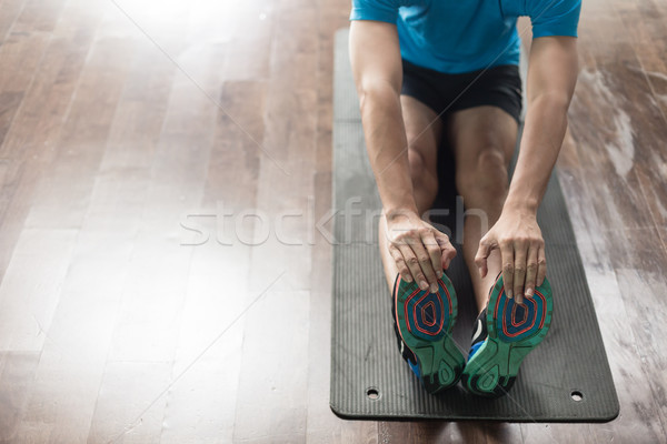 High-angle view of the hands of a man touching his toes as a stretching exercise Stock photo © Kzenon