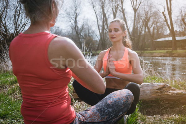 Two woman practicing yoga on a tree stump by the river Stock photo © Kzenon