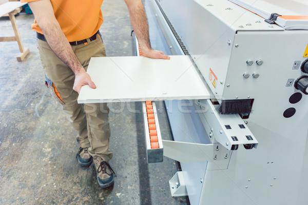 Carpenter in furniture factory working on veneer machine Stock photo © Kzenon