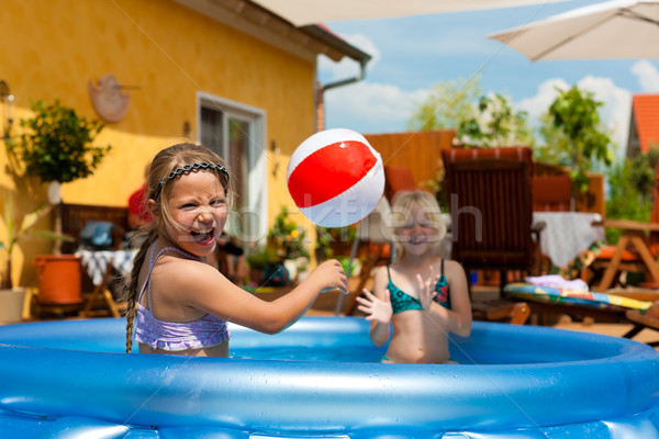 Stock photo: Children playing with ball in water pool