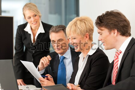 Young realtor explaining ground plan to couple Stock photo © Kzenon