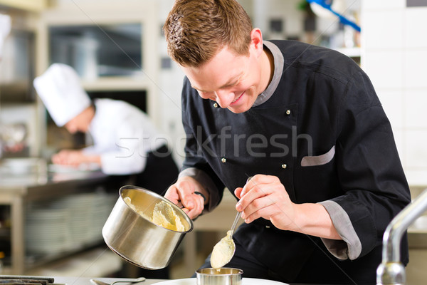 Chef in restaurant kitchen preparing food Stock photo © Kzenon
