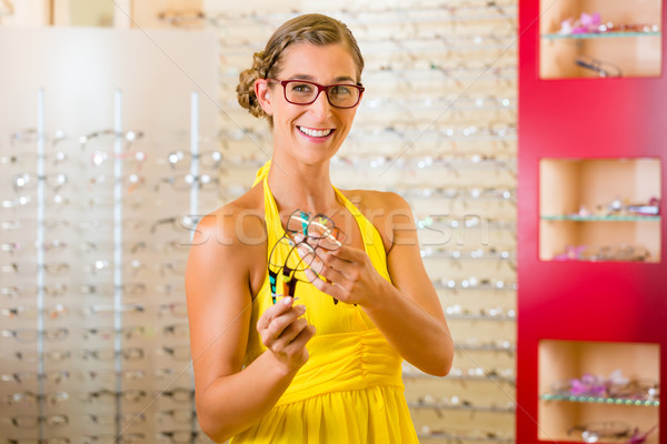 Young woman at optician with glasses Stock photo © Kzenon