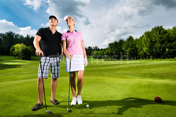 Stock photo: Young sportive couple playing golf on a course