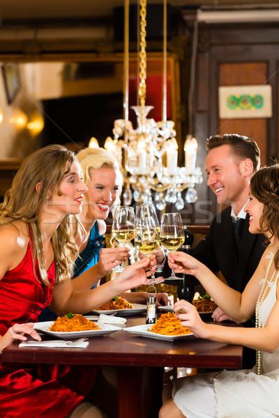 Friends in a very good restaurant clink glasses Stock photo © Kzenon