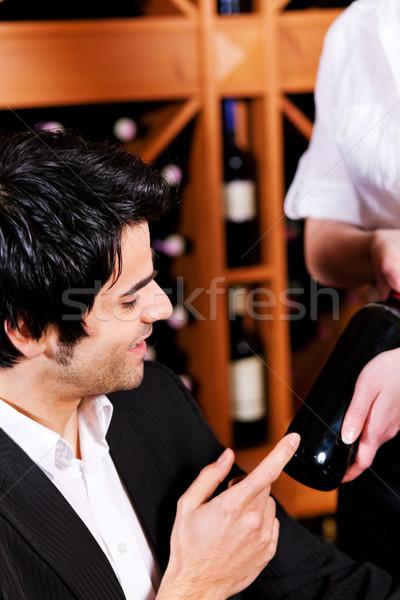 Waitress offers a bottle of red wine  Stock photo © Kzenon
