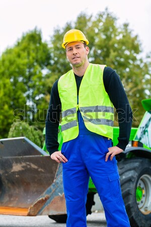 Builder on site in front of  construction machinery Stock photo © Kzenon