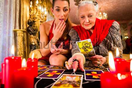 Soothsayer during a session doing palmistry Stock photo © Kzenon