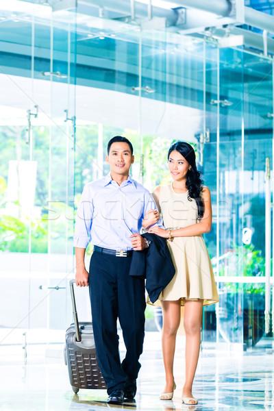 Asian couple walking in hotel lobby with suitcase Stock photo © Kzenon