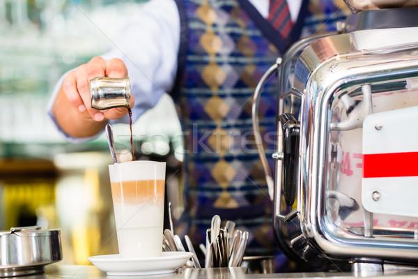 Barista in cafe pouring espresso shot in latte macchiato Stock photo © Kzenon
