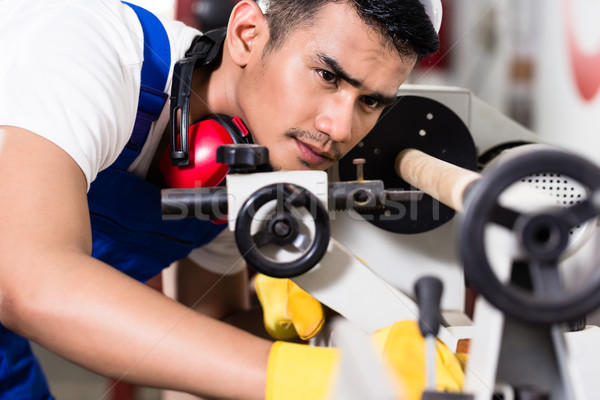 Worker adjusting turning machine in factory  Stock photo © Kzenon