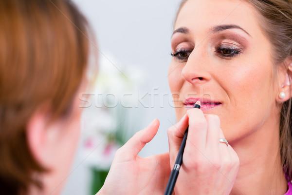 Beautician applying lip color on woman Stock photo © Kzenon