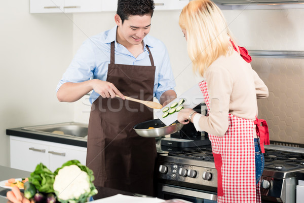 Asian couple cooking vegetables in frying pan Stock photo © Kzenon