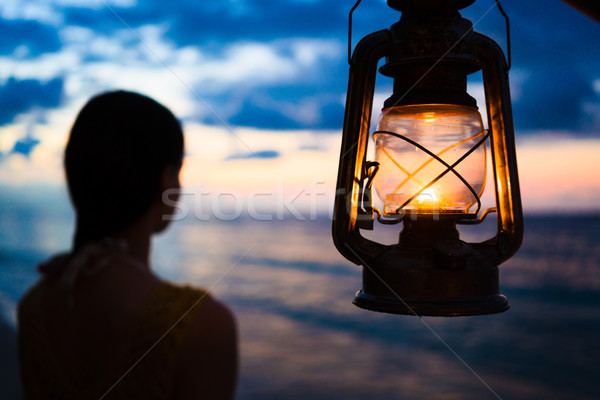 Woman in lantern shine looking to sea at sunset  Stock photo © Kzenon