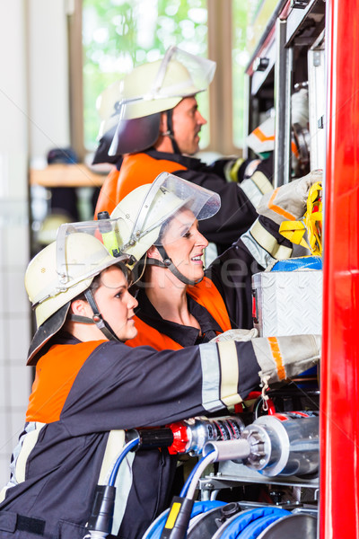 Fire fighters attaching hose at hose laying vehicle Stock photo © Kzenon