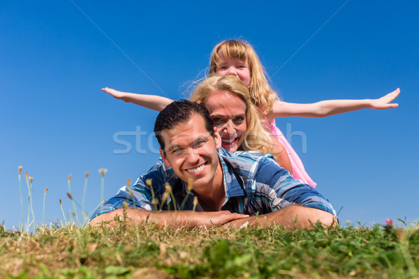 Girl playing airplane on back of parents Stock photo © Kzenon