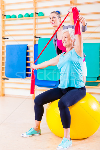 Senior woman with stretch band at fitness Stock photo © Kzenon