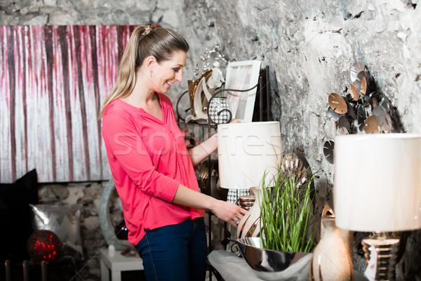 Female customer in furniture store looking at shade lamp wanting Stock photo © Kzenon
