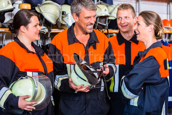 Male and female fire fighters in chat at work Stock photo © Kzenon