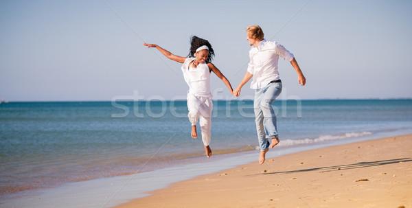 Couple in vacation on beach, black woman and white man Stock photo © Kzenon