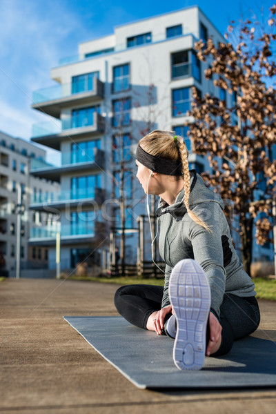 Fit young woman stretching her leg during outdoor warm-up exerci Stock photo © Kzenon