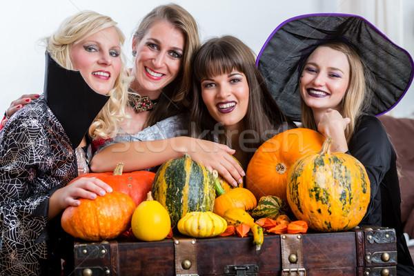 Four cheerful women celebrating Halloween together during costum Stock photo © Kzenon
