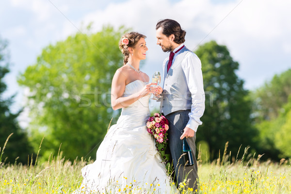 Bridal pair celebrate wedding day with champagne Stock photo © Kzenon